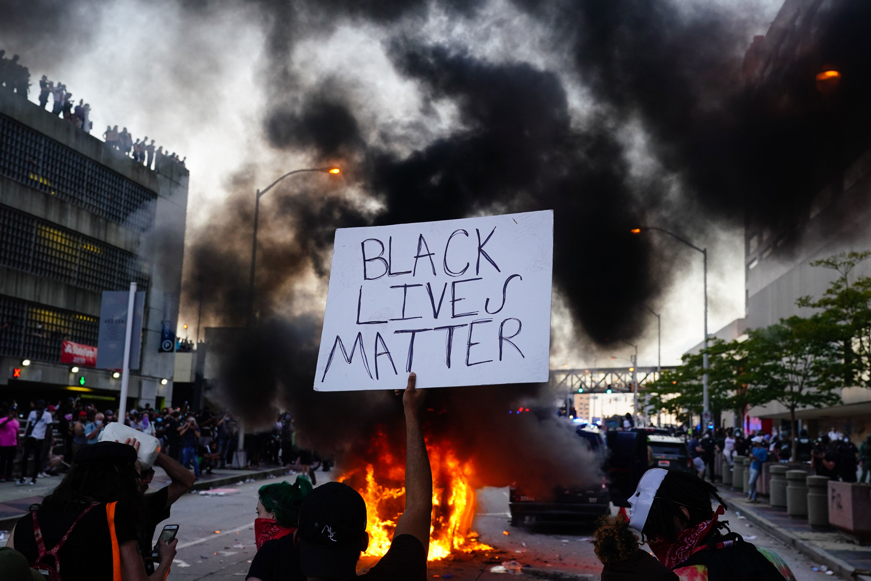 A man holds a Black Lives Matter sign as a police car burns in Atlanta on May 29.
