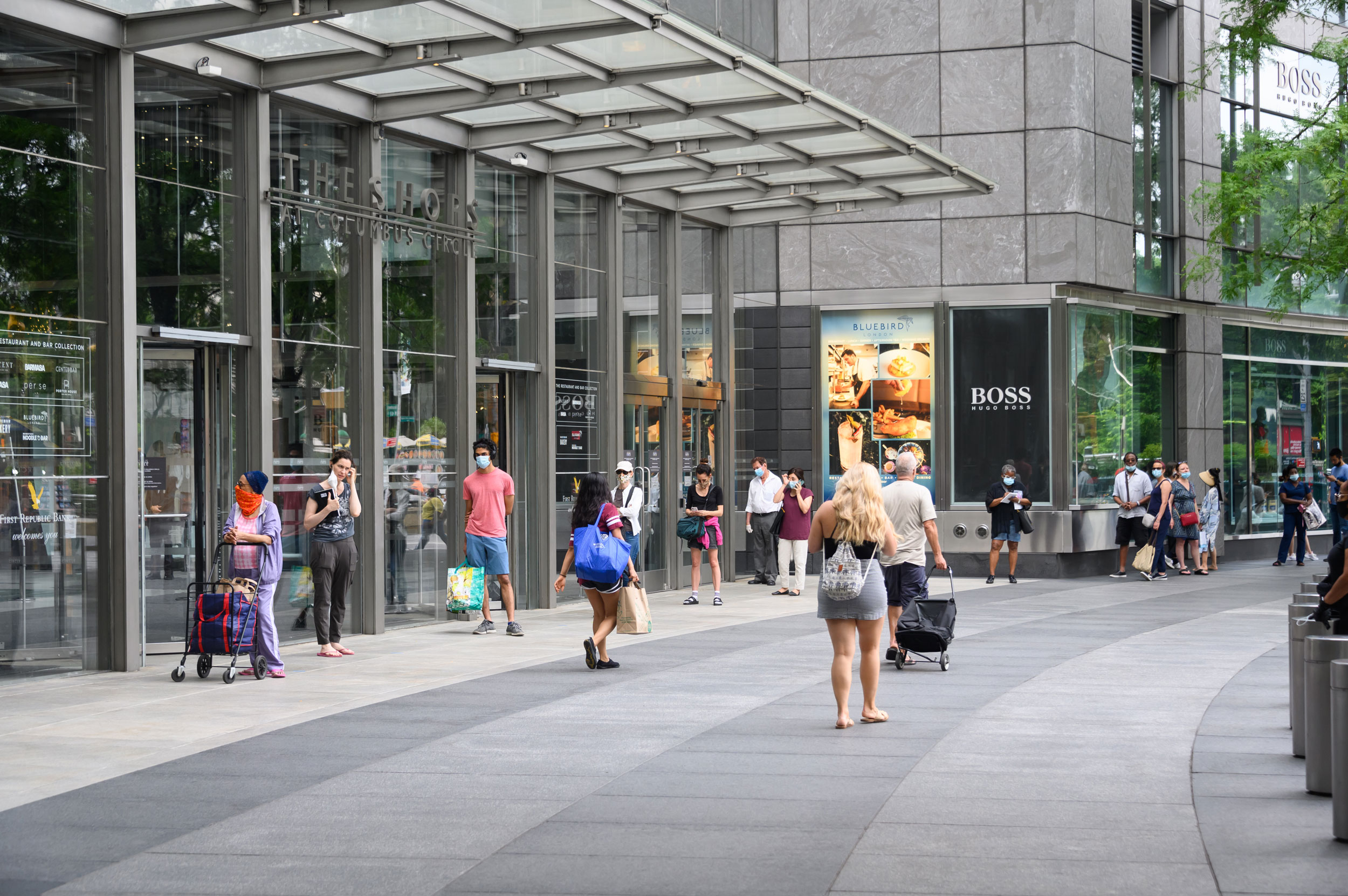People stand in line outside The Shops at Columbus Circle on July 7,