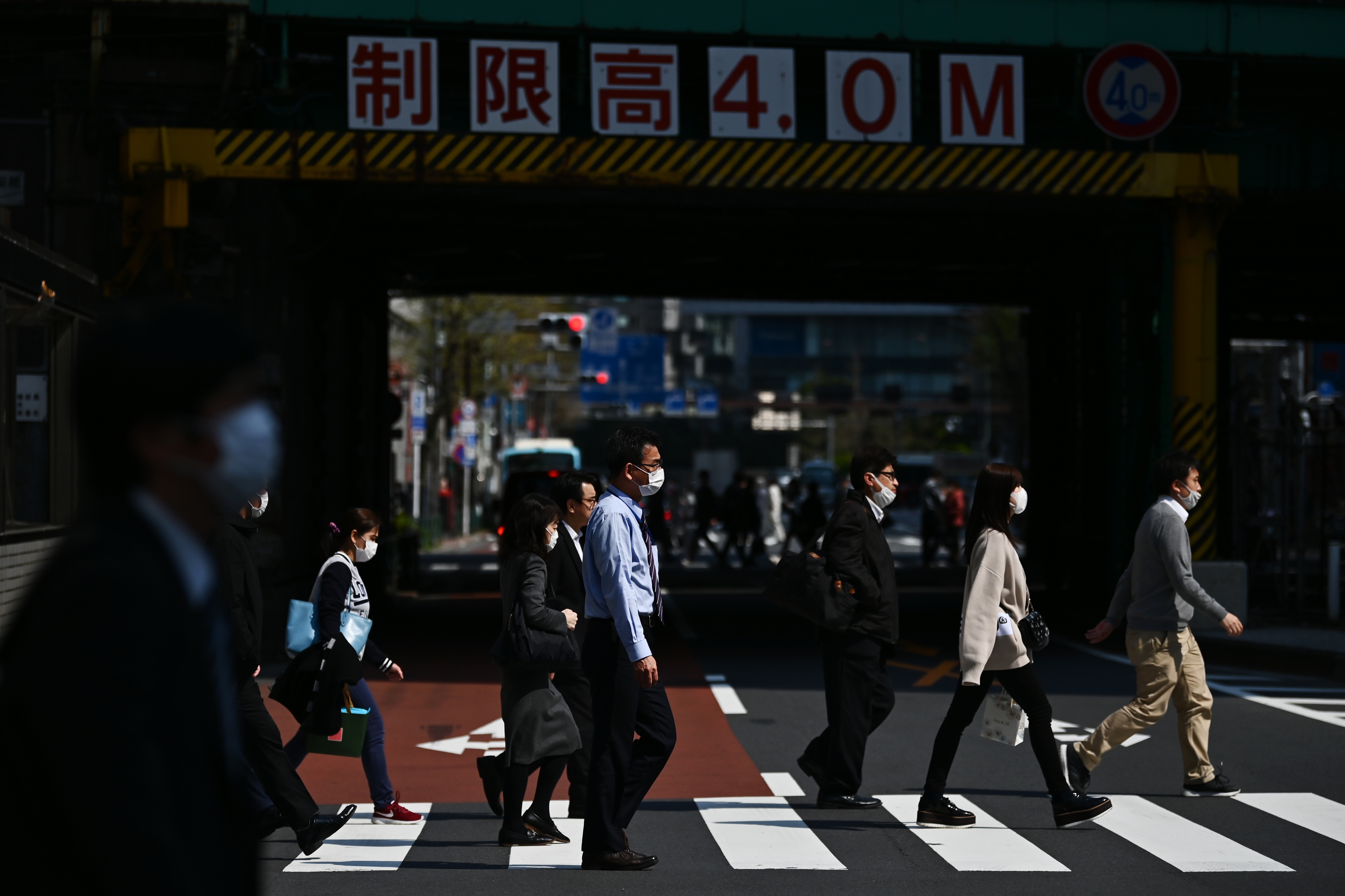 People cross a street in Tokyo on April 8.
