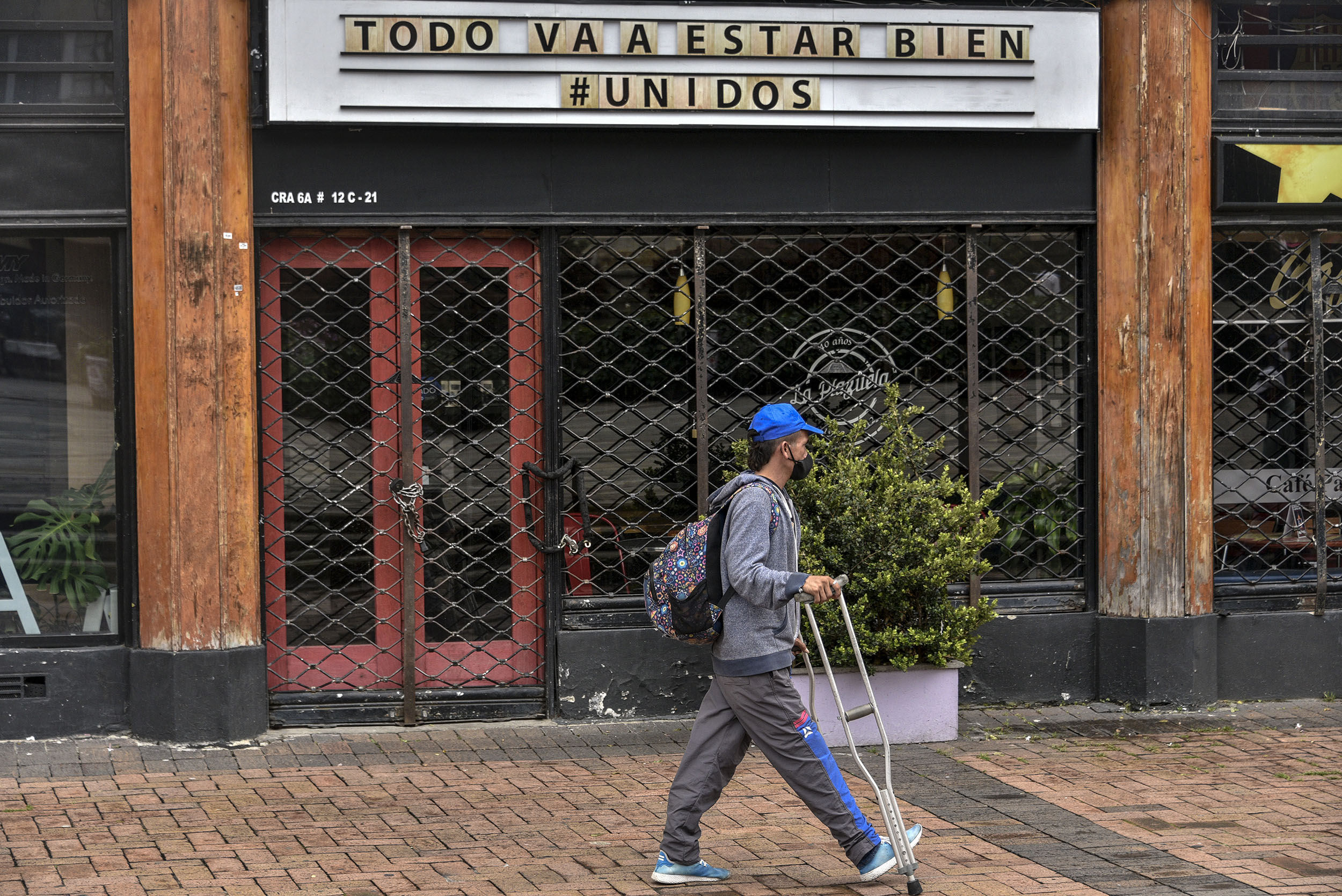 A passer-by walks past a closed restaurant with the sign that reads 'everything will be alright' on July 02, in Bogota, Colombia.