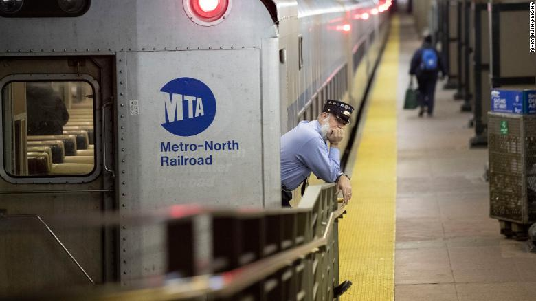 A conductor waits for customers to embark a train at Grand Central Terminal on Tuesday.