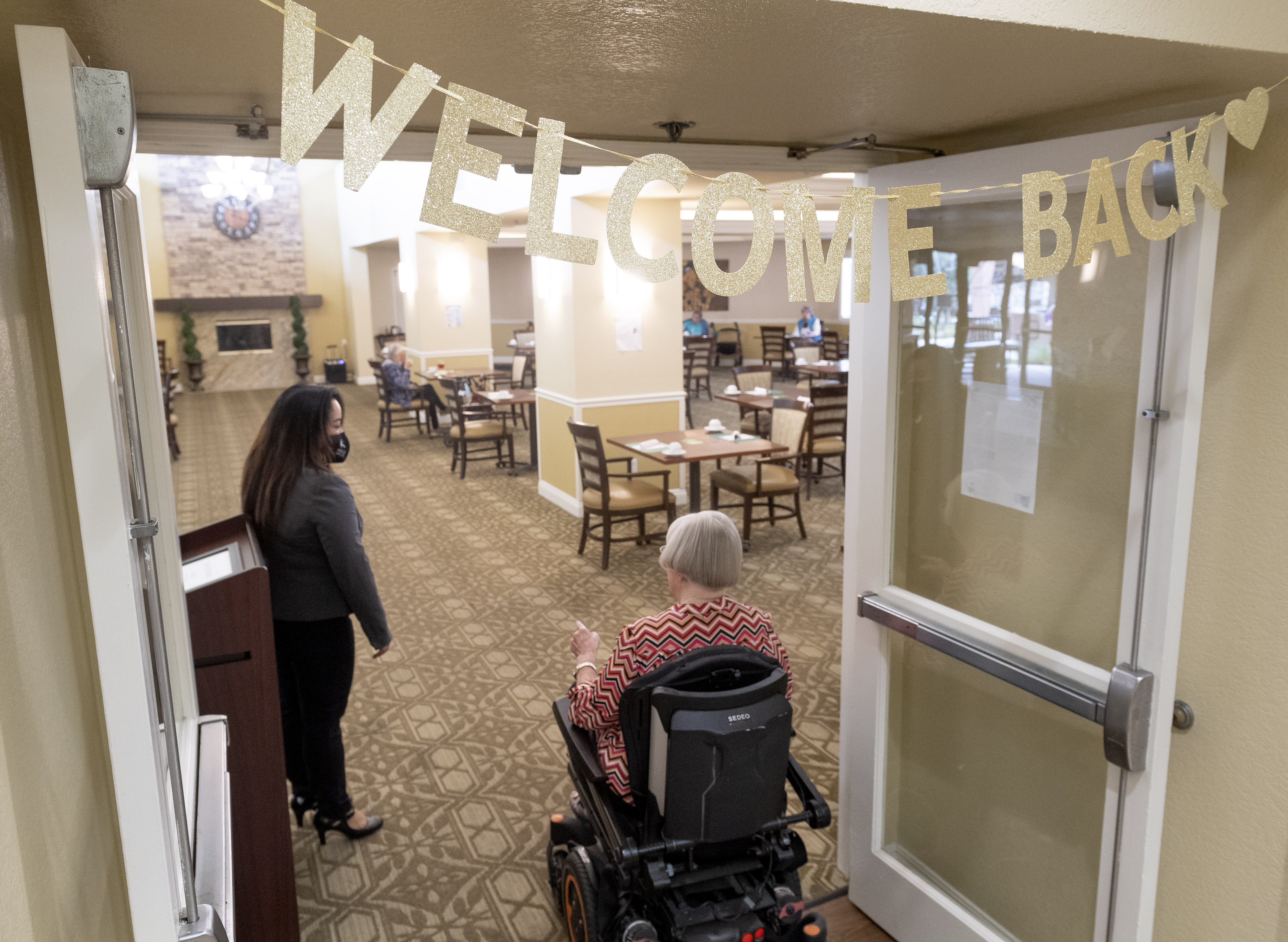 Executive Director Patricia Gustin greets residents entering the dining room at a nursing home in Anaheim, California, on March 8.
