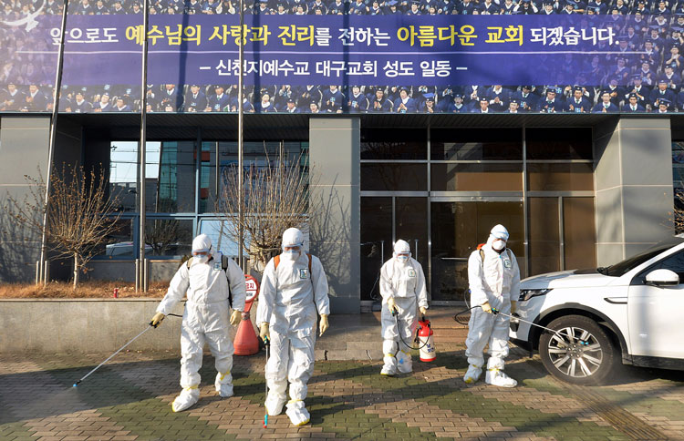 Workers wearing protective gear spray disinfectant against the coronavirus in front of a church in Daegu, South Korea, on Wednesday, February 19.