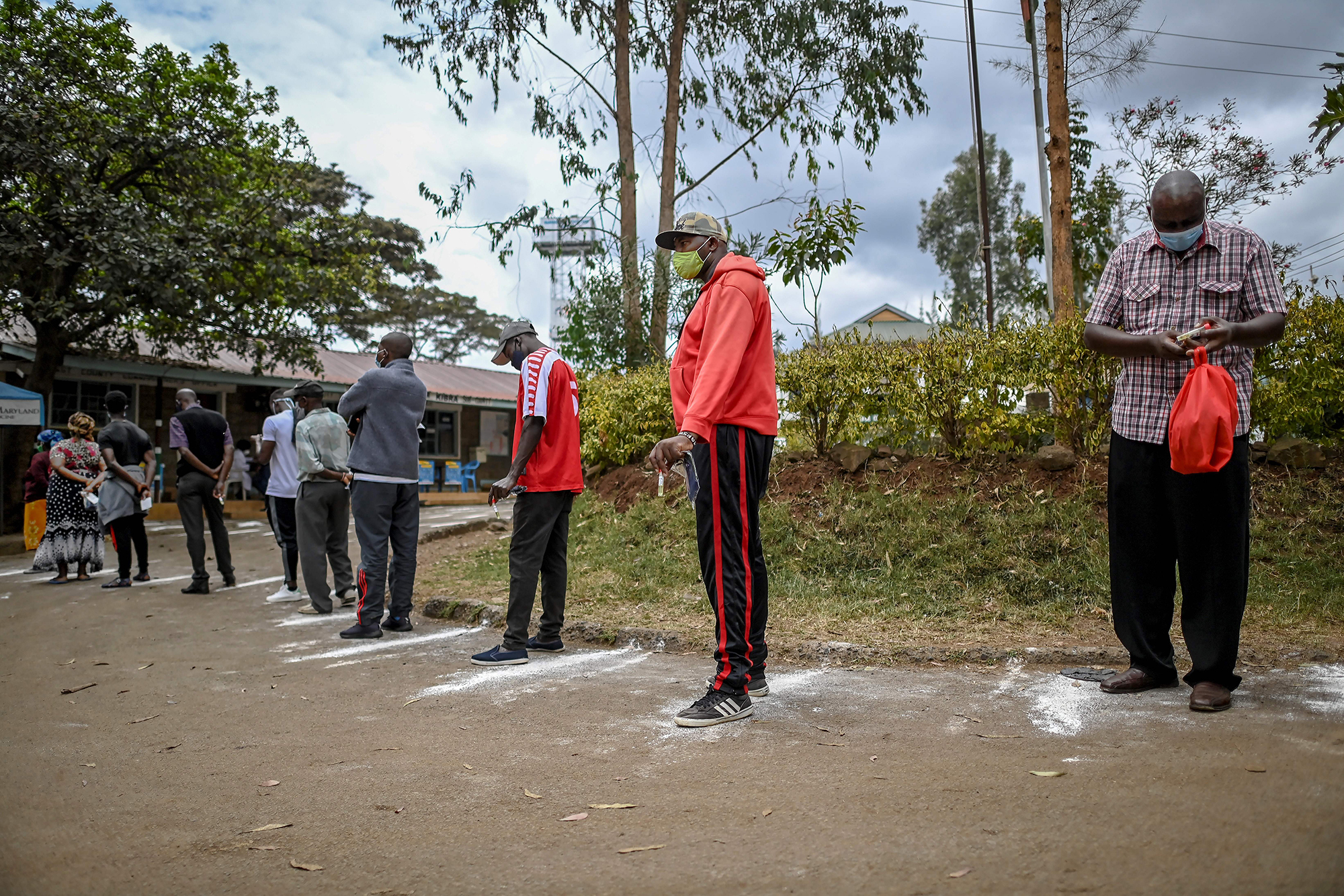 People stand on social distancing markers as they wait to be tested for Covid-19 in the Kibera slum of Nairobi, Kenya, on October 18.
