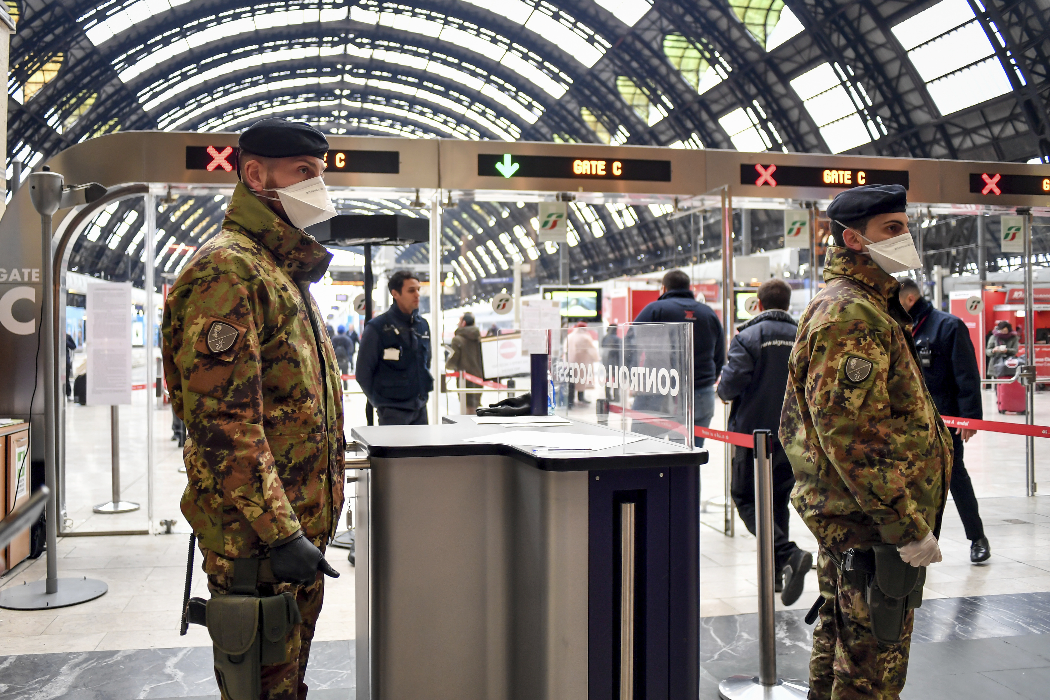 Italian soldiers patrol the gates at the Milan main train station on Monday.