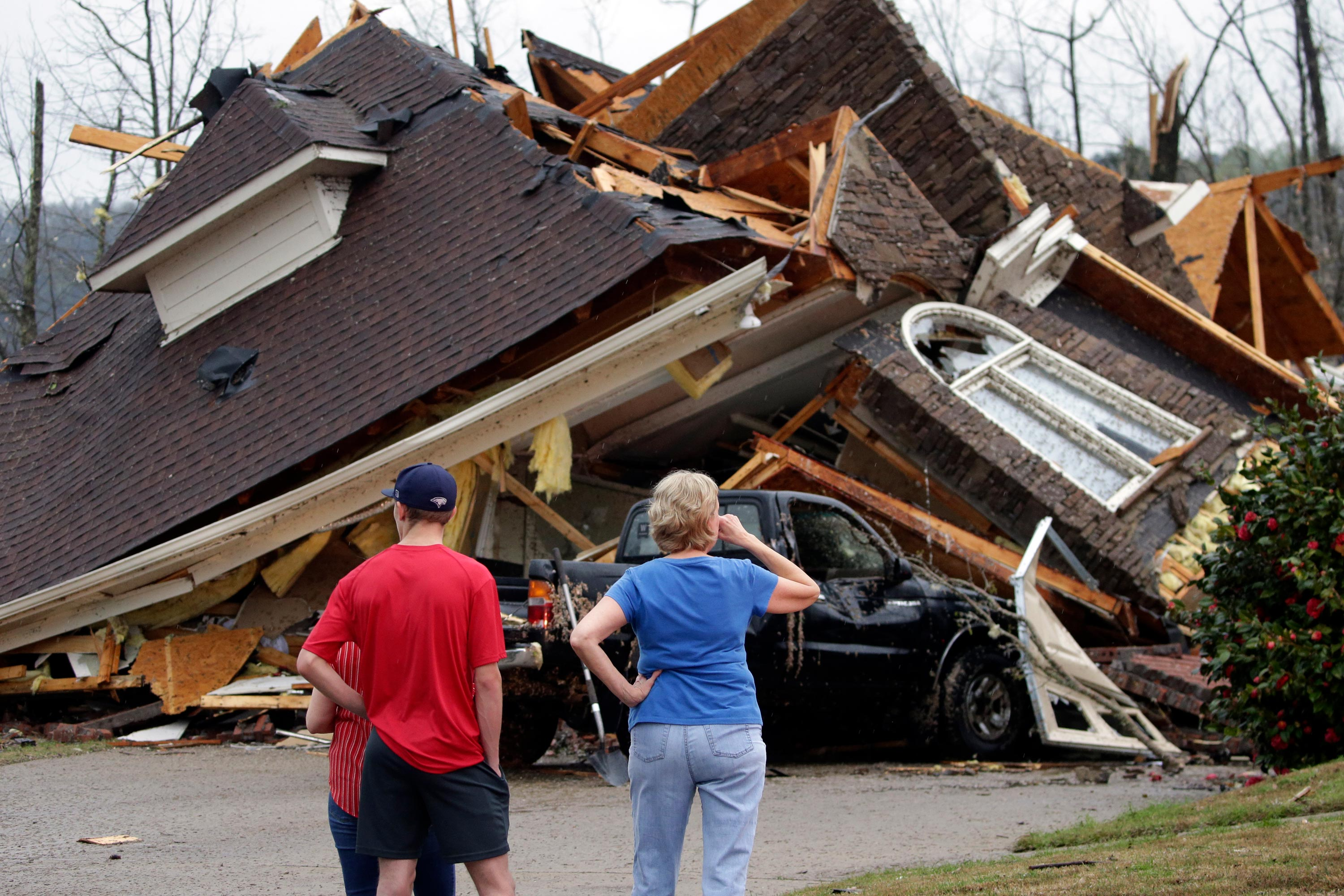 Residents survey damage to homes after a tornado touched down south of Birmingham, Alabama, in the Eagle Point community damaging multiple homes on March 25.