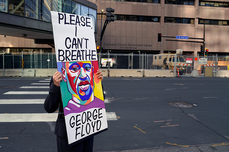 A protester holds a sign across the street from National Guard soldiers guarding the Hennepin County Government Center Tuesday, April 6, 2021, in Minneapolis where testimony continues in the trial of former Minneapolis police officer Derek Chauvin.