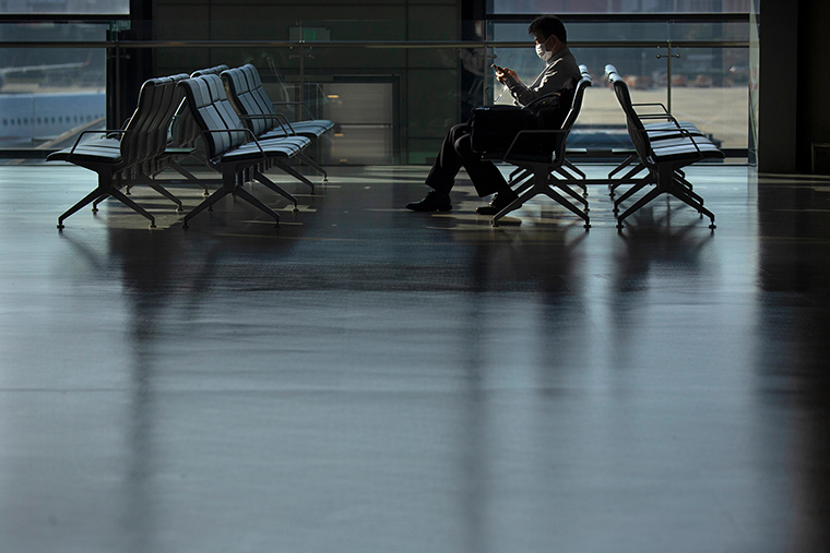 A traveler wearing a face mask to protect against the coronavirus sits at a boarding gate at the Shanghai Hongqiao International Airport in Shanghai, Friday, Nov. 6, 2020.
