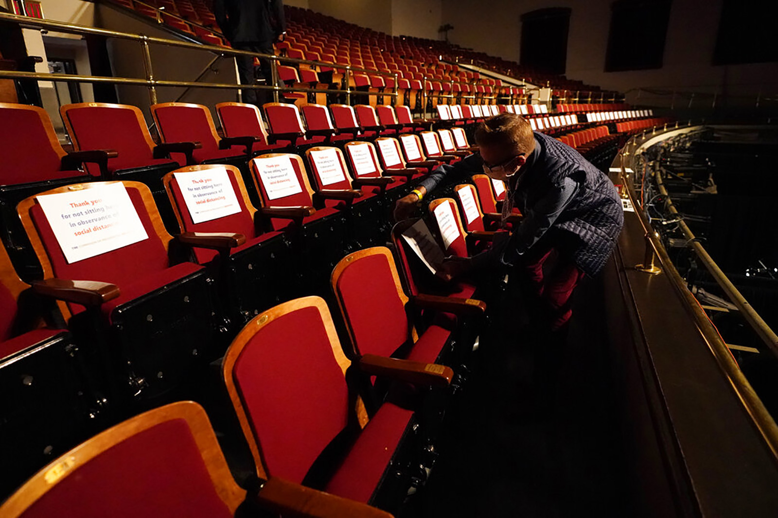 A member of the production staff puts labels on seats in an effort to keep seats socially distanced ahead of the vice presidential debate at the University of Utah, On Wednesday in Salt Lake City.