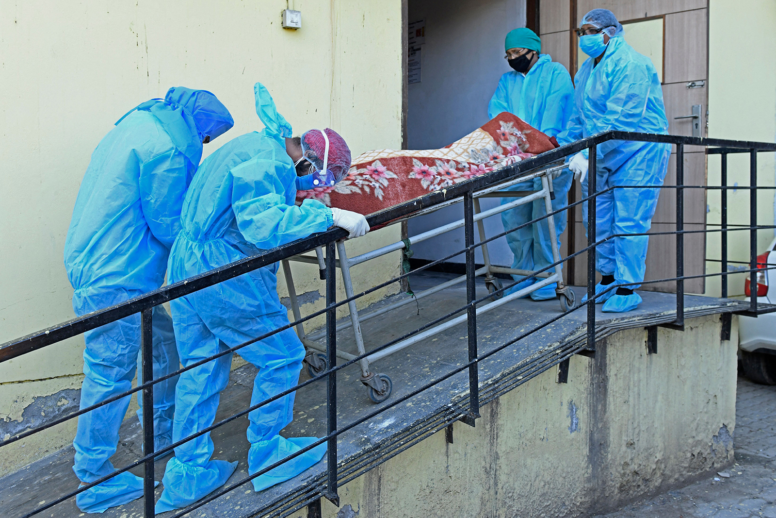 Members of medical staff wearing protective gear carry the dead body of a Covid-19 victim at a hospital in Amritsar, India on April 24.