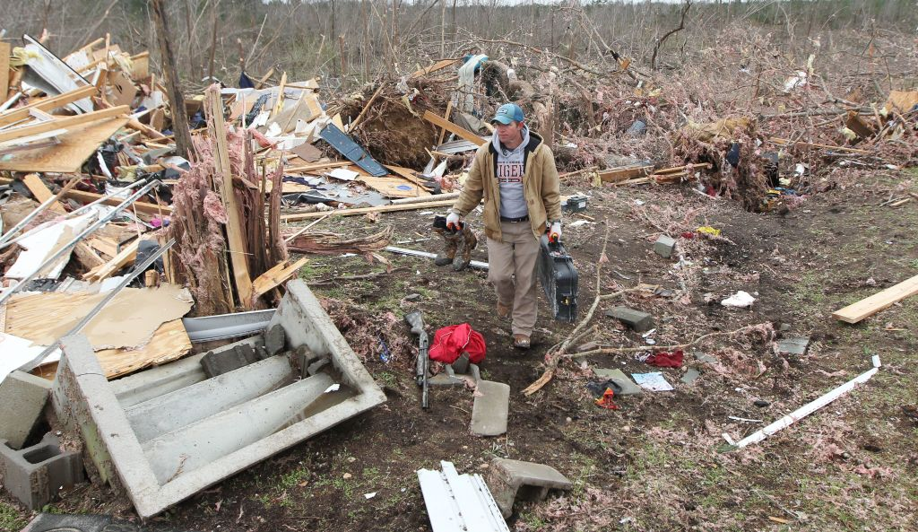 Joey Roush carries items from his mother's home after it was destroyed in a tornado in Beauregard, Alabama, on March 4, 2019.