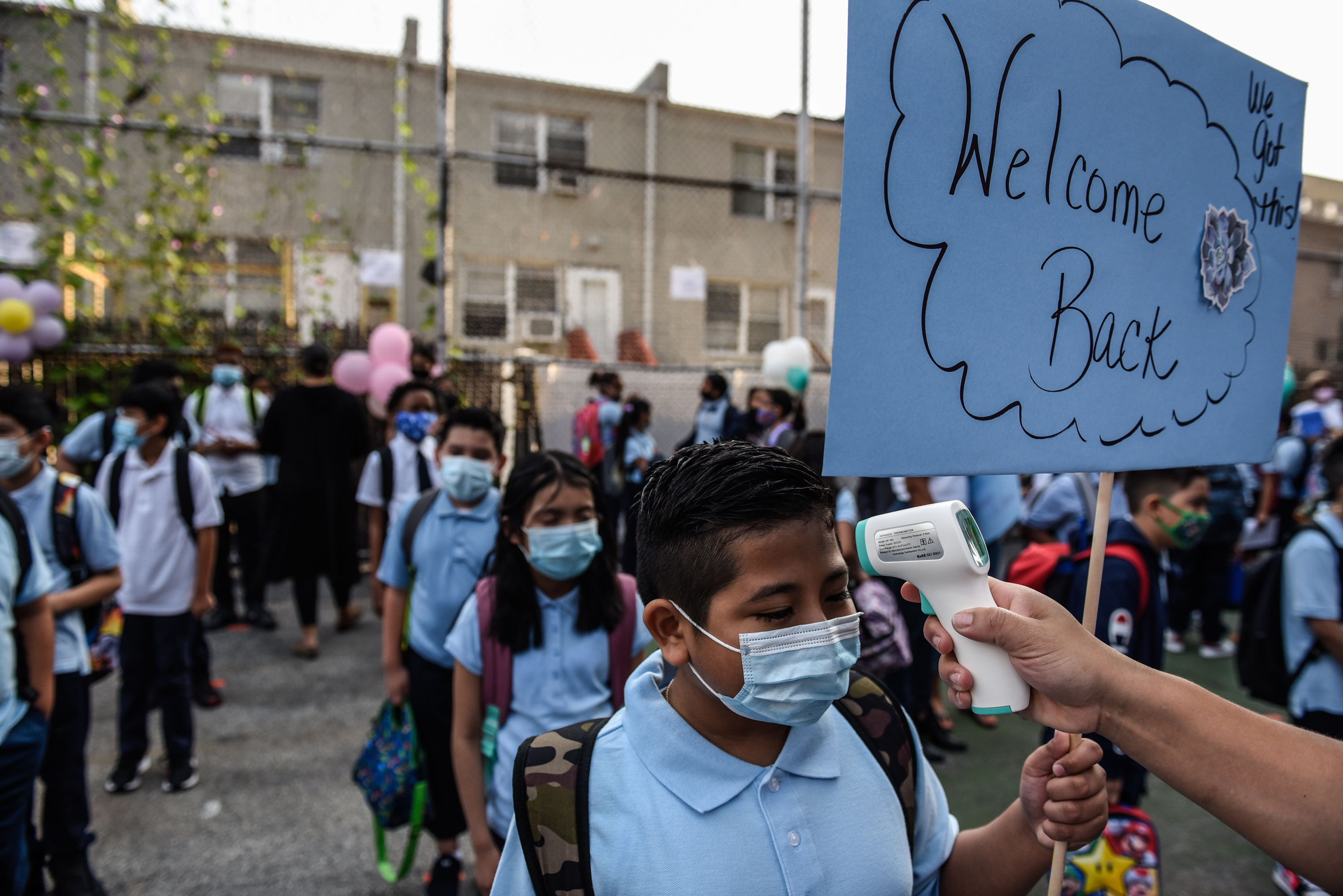 Students wait in line to get their temperature taken before entering a public school in the Bronx on September 13.