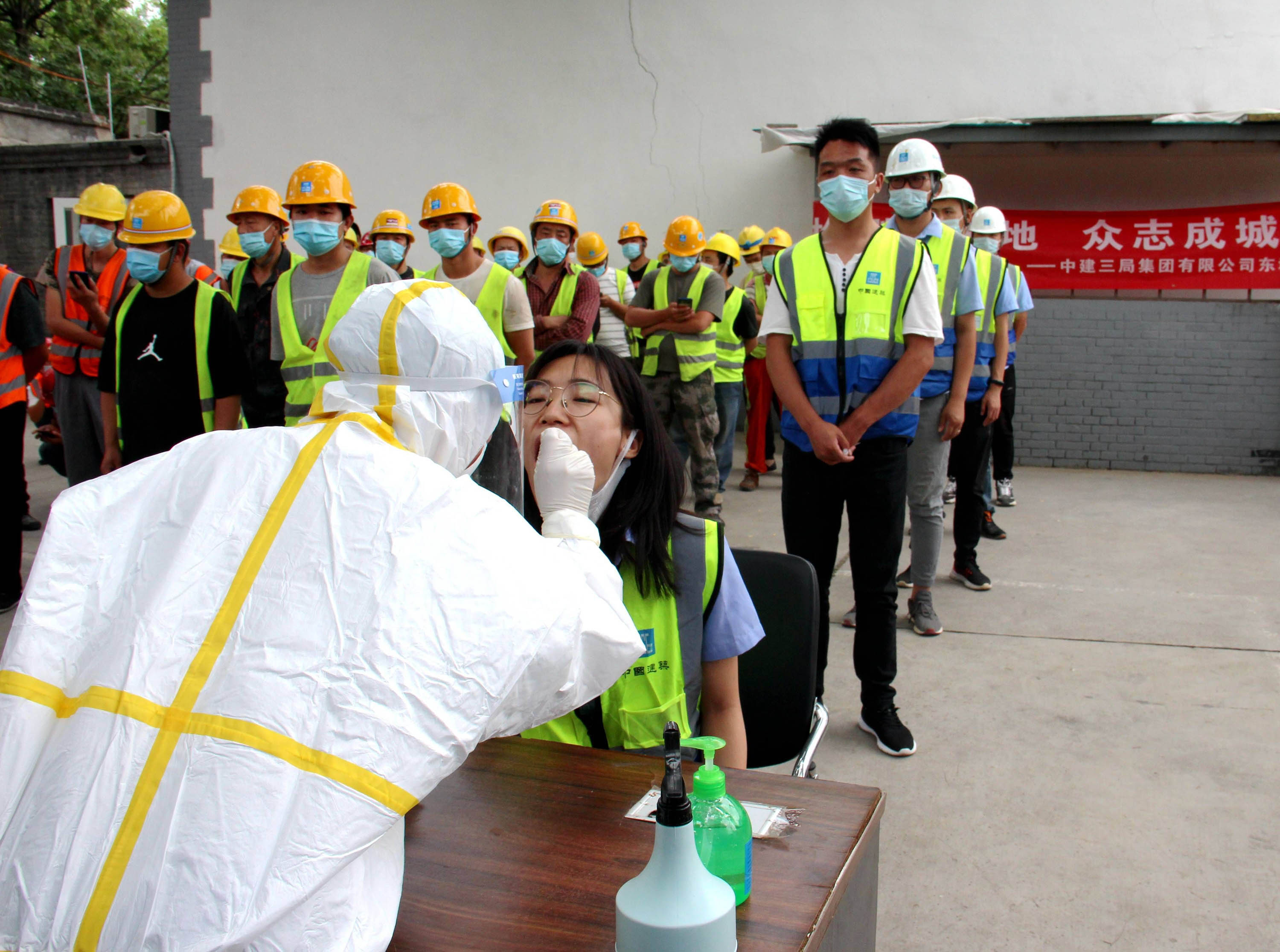 A medical worker collects throat swabs from construction workers at a construction site in Beijing on June 17.