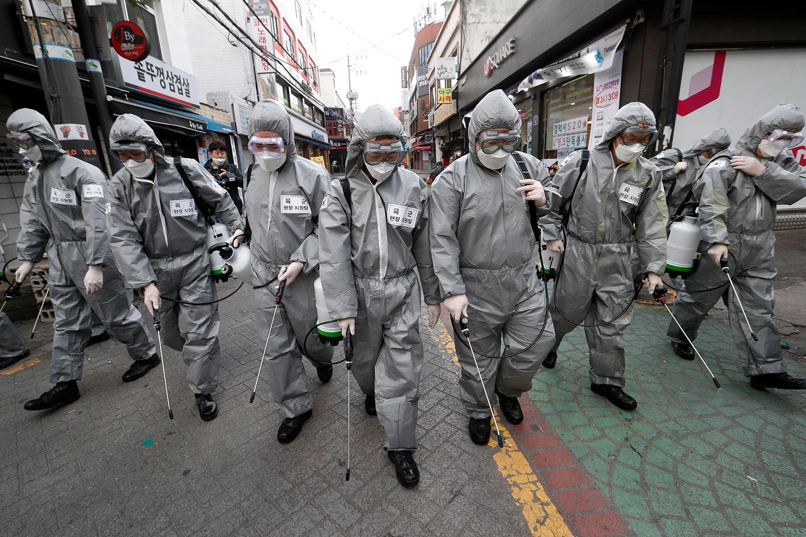 Army soldiers wearing protective suits spray disinfectant as a precaution against the new coronavirus at a shopping street in Seoul on March 4.
