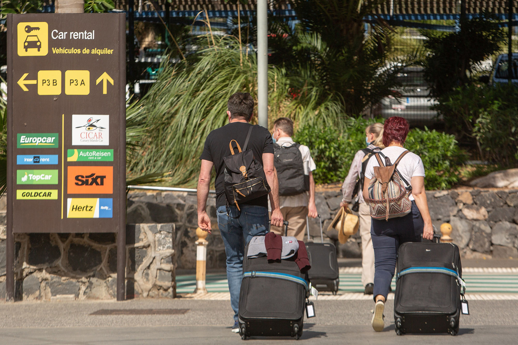 People walk with their luggage upon their arrival to the Reina Sofia Tenerife-South airport on the Canary Island of Tenerife on October 31.