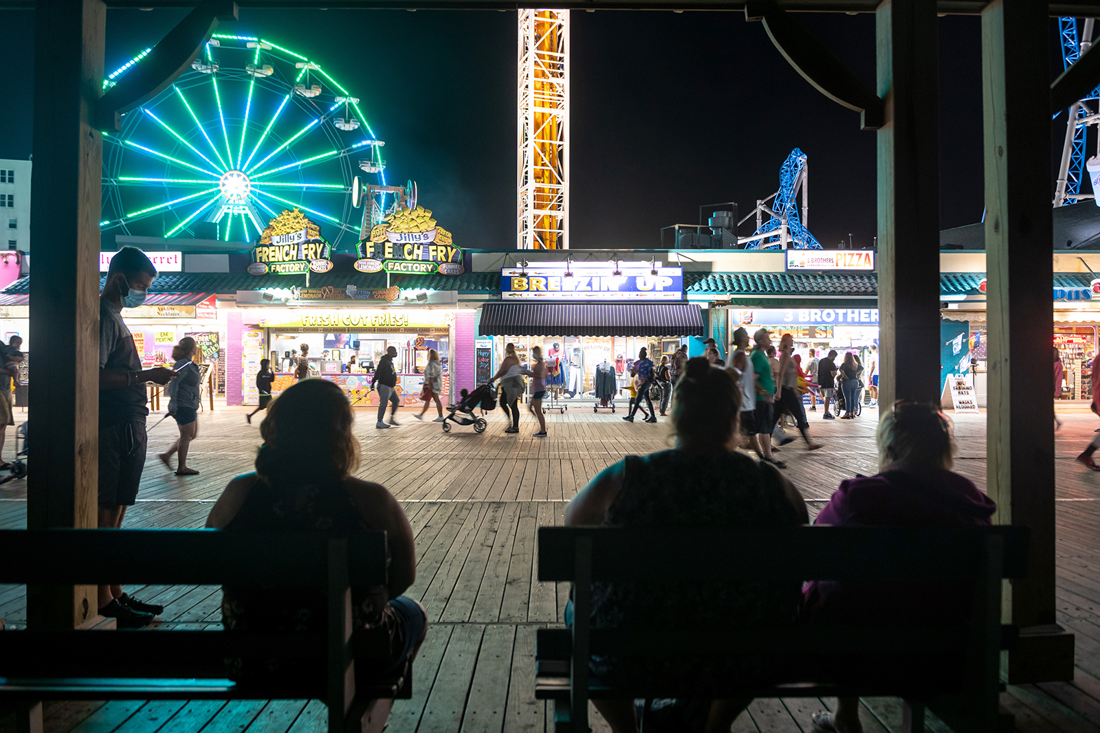 People sit on benches facing the ferris wheel in Ocean City, New Jersey on September 7.