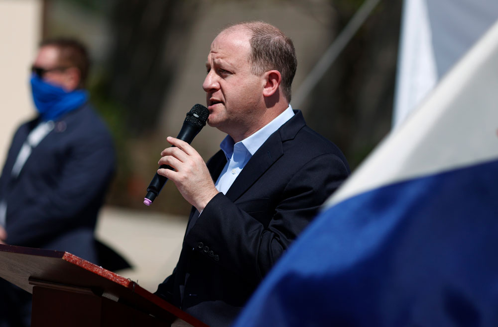 Colorado Governor Jared Polis makes a point about the state's efforts to rein in the new coronavirus during a news conference outside the Stride Community Health Center on Monday, May 18, in Wheat Ridge, Colorado.