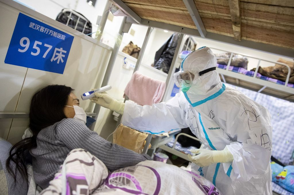 A medical worker checks the body temperature of a patient at an exhibition center converted into a hospital in Wuhan in China's central Hubei province on Friday, February 17.