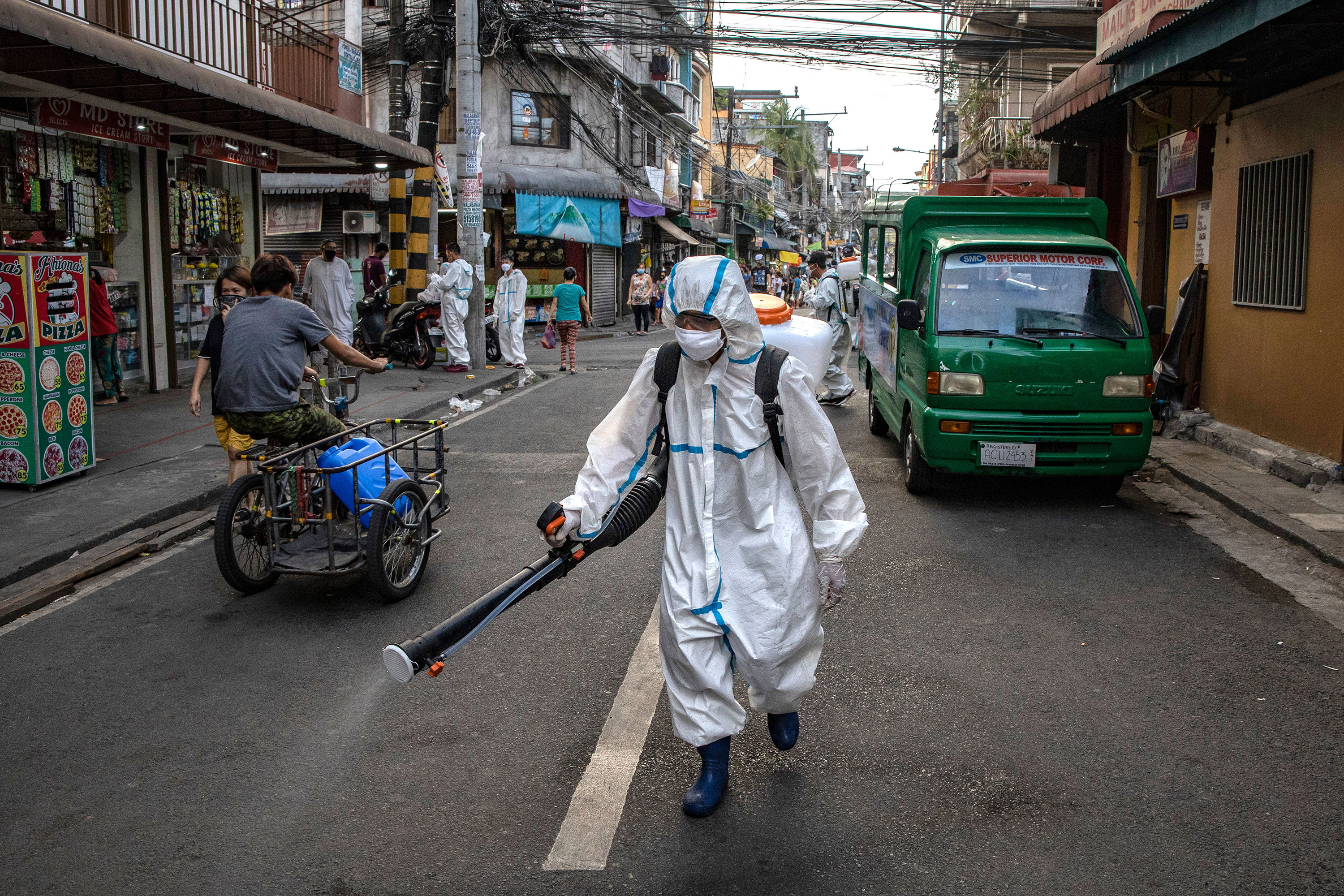 A worker sprays disinfectant along a street in San Juan, Metro Manila, Philippines on March 23.