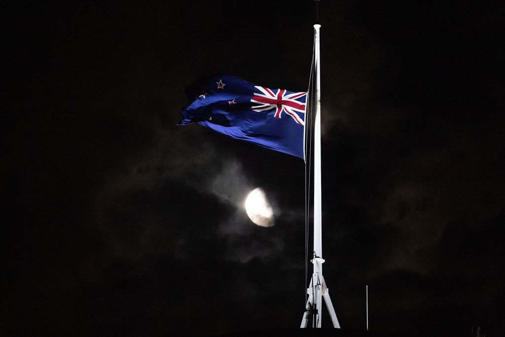 The New Zealand flag flies at half-mast outside the Parliament building in Wellington on Friday evening.