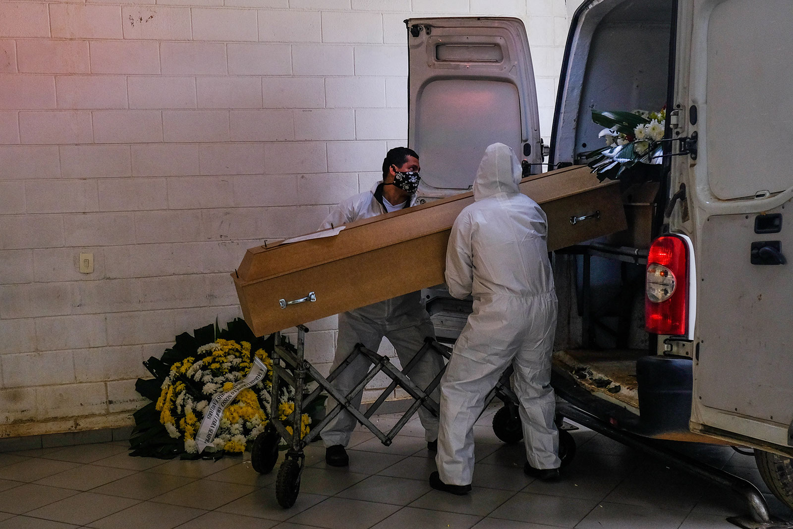 Employees at the Vila Formosa cemetery unload a coffin from a van in San Paulo, Brazil, on May 23.