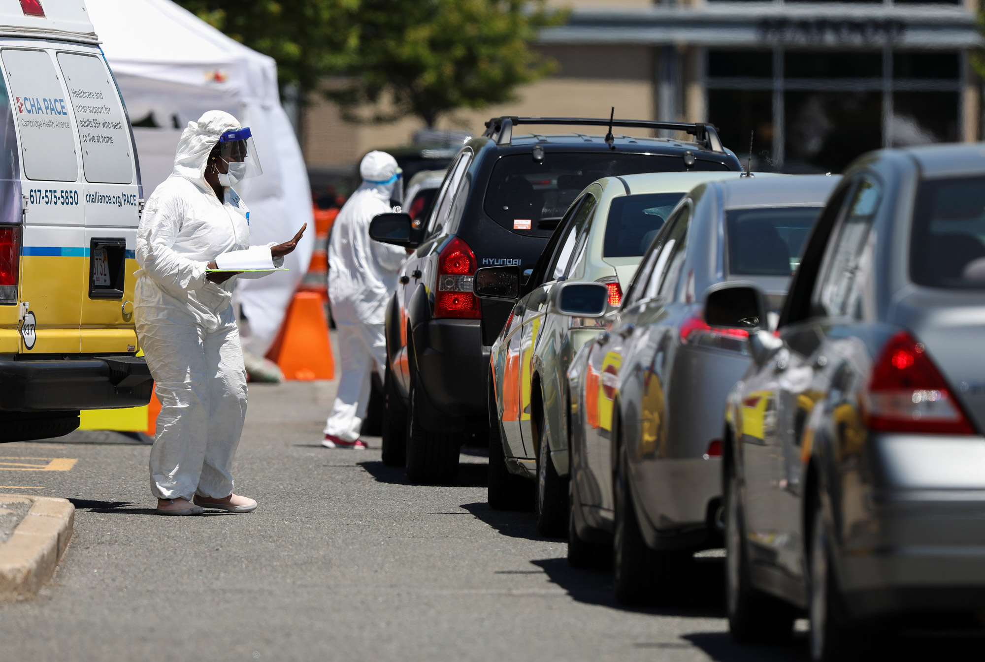 Medical workers take down personal information from those driving in at a Coronavirus testing location in the Cambridge Health Alliance Testing Tent in Cambridge, Massachusetts, on June 18.