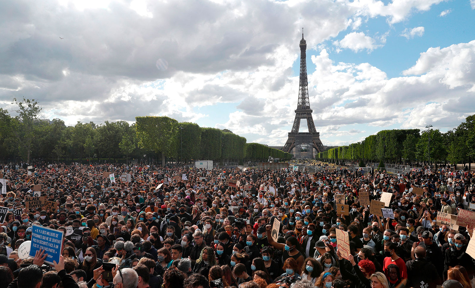 People gather on Champ de Mars in front of the Eiffel Tower in Paris on June 6.