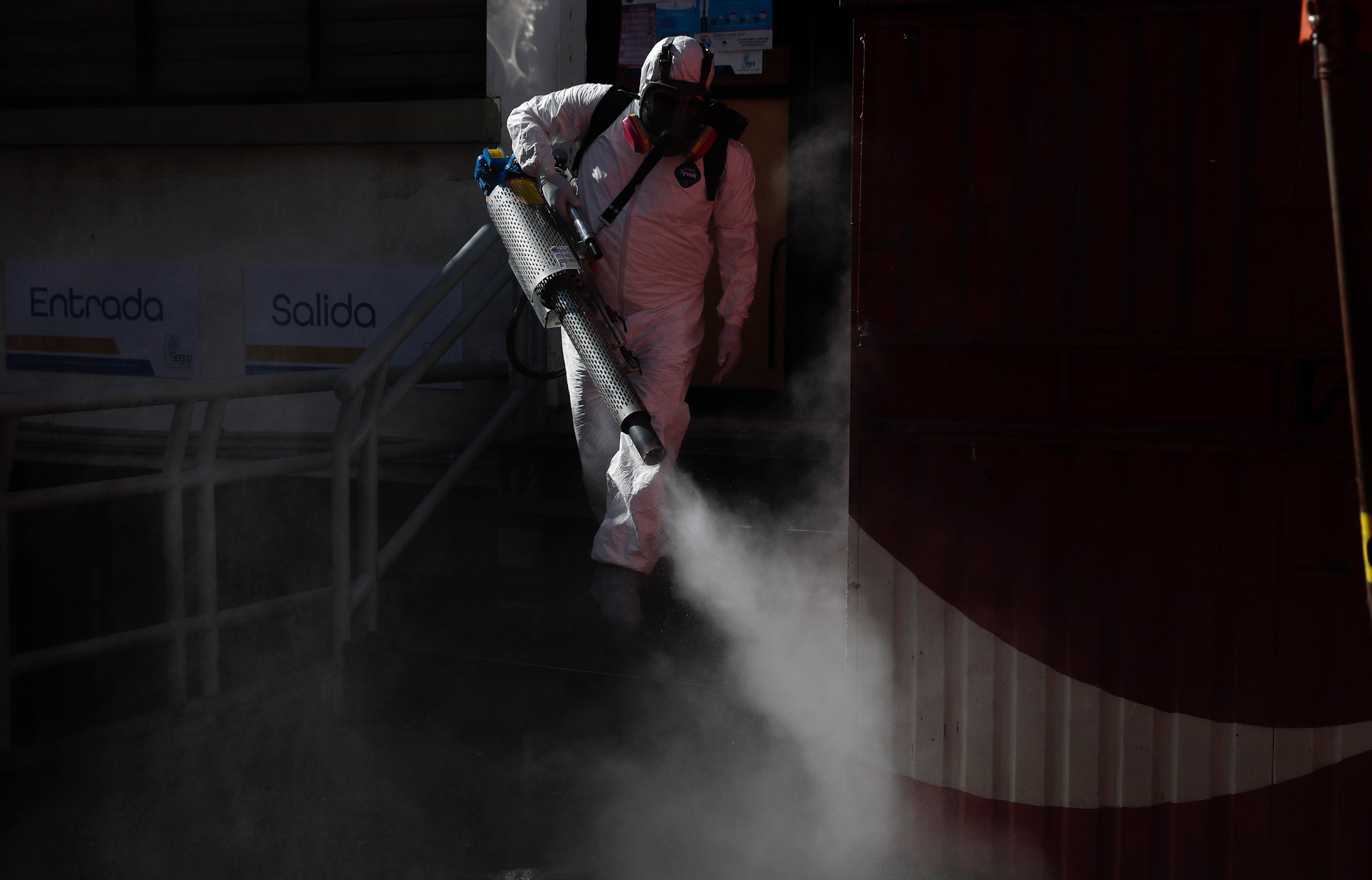 A city worker disinfects the entrance to the government identification office in La Paz, Bolivia, on June 16.