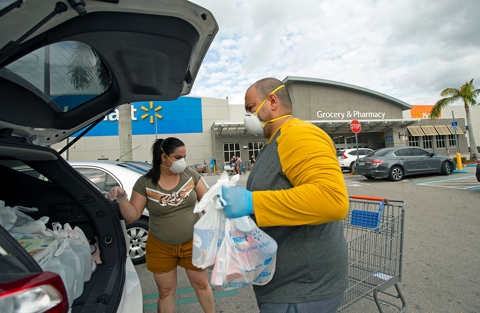 Joel Porro and Lizz Hernandez wear gloves and protective masks as they put bags in the trunk of their car after shopping at Walmart Supercenter in Miami.