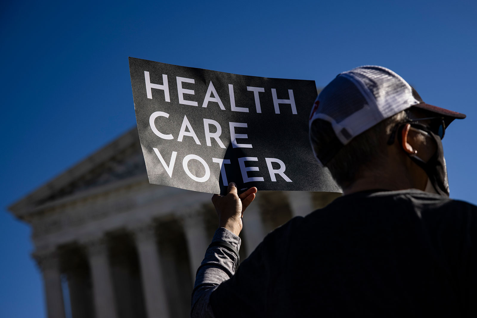 A supporter of the Affordable Care Act stands in front of the Supreme Court in November 2020.