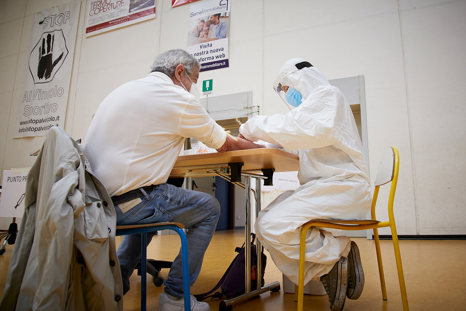 A heath worker wearing PPE takes a blood sample from a man in Cisliano, Italy on April 28.