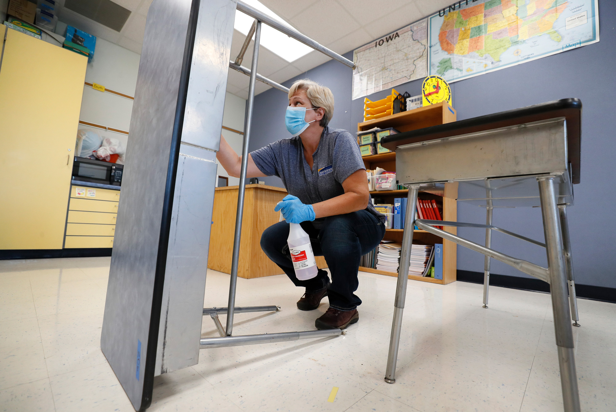 Des Moines Public Schools custodian Cynthia Adams cleans a desk in a classroom at Brubaker Elementary School on July 8 in Des Moines, Iowa.