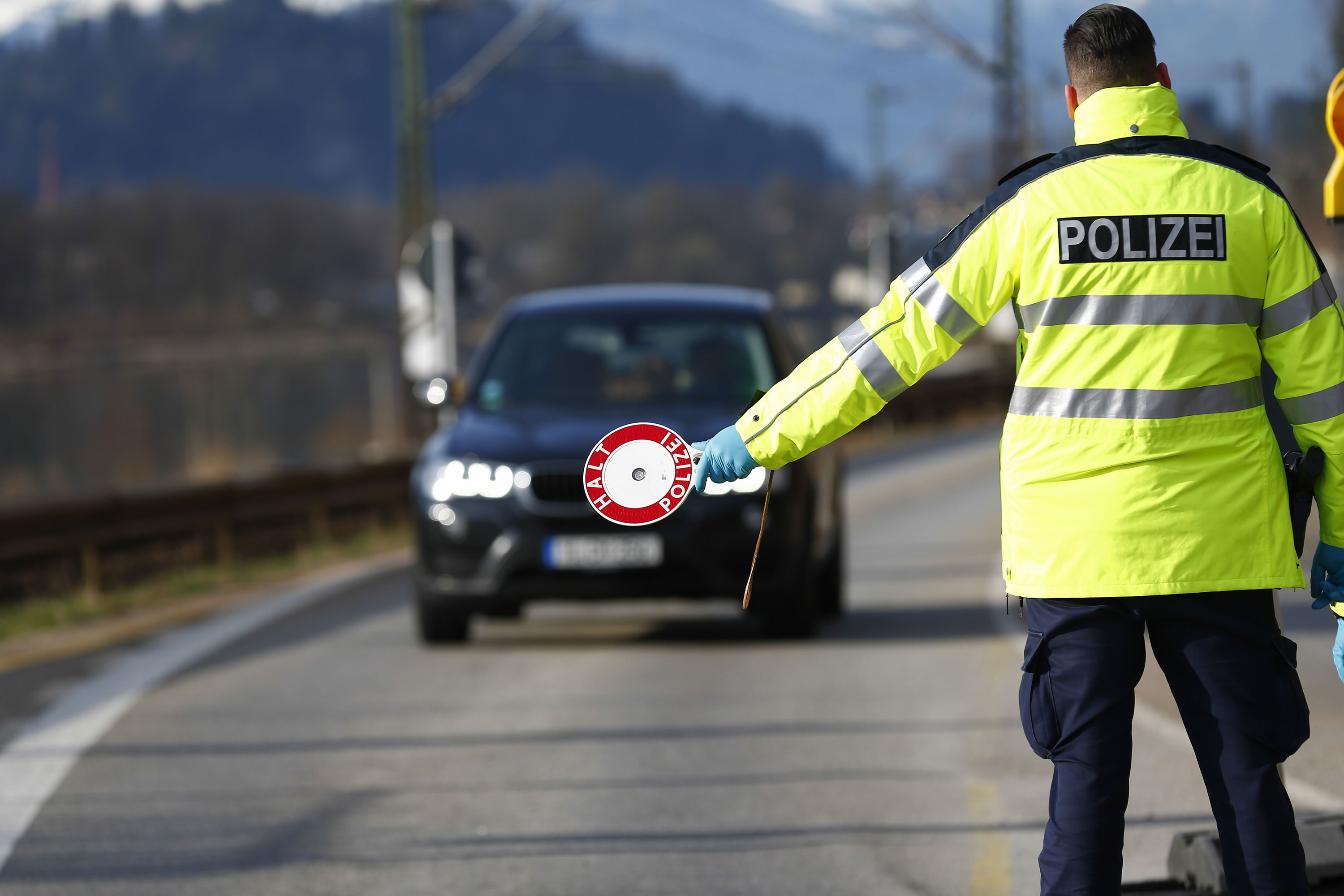 A police officer halts traffic on Germany's border with Austria to check drivers' paperwork in Kiefersfelden, Germany, on March 17.