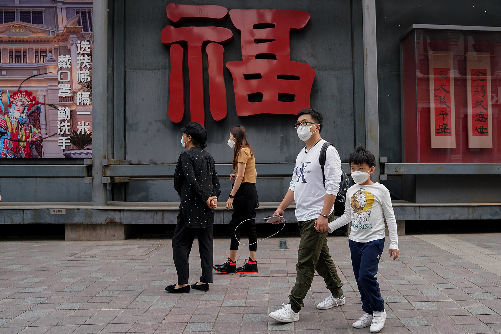 Shoppers wear protective masks as they walk on a commercial street on May 8, in Beijing.