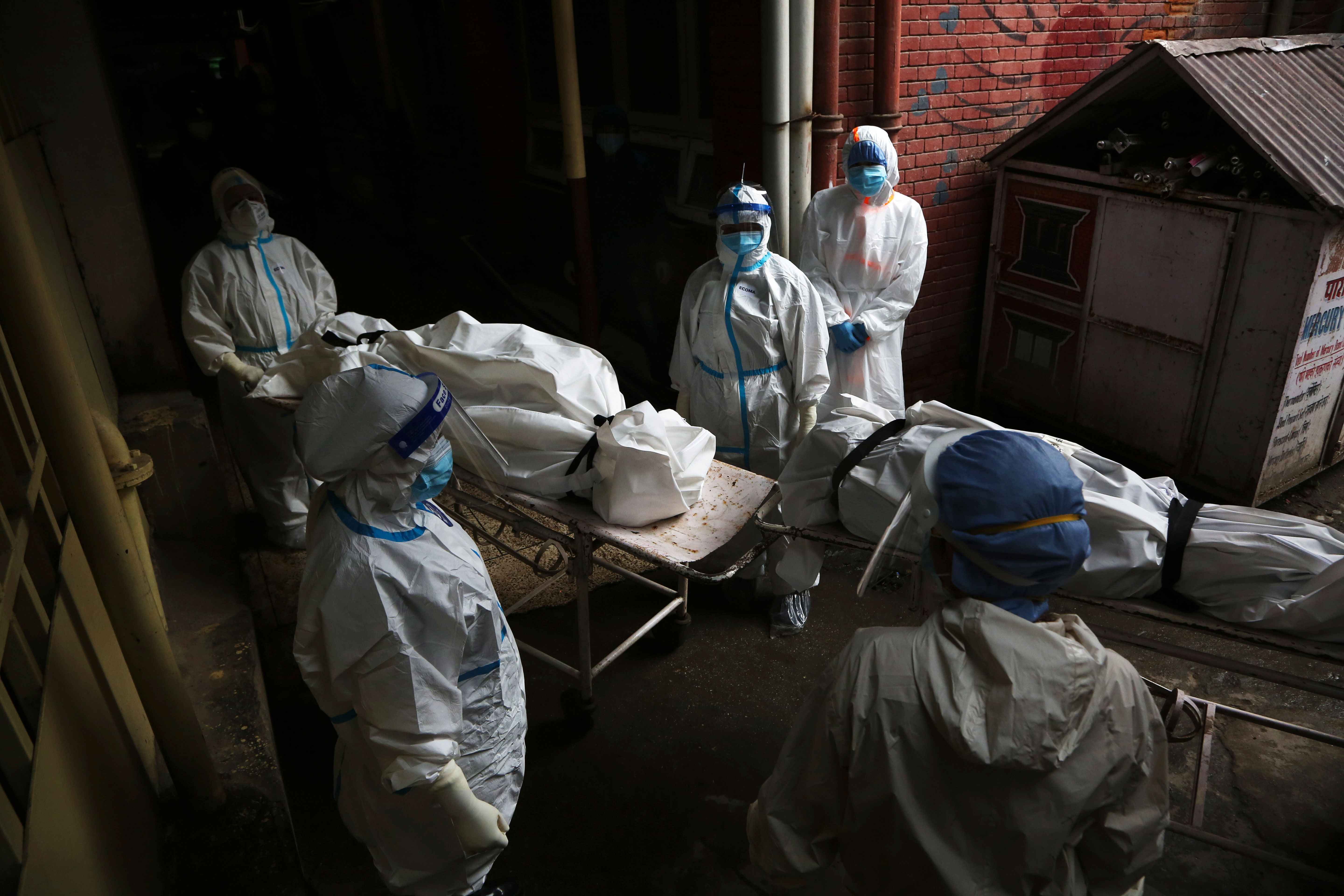 Paramedics get ready to load the bodies of Covid-19 victims into an ambulance for cremation in Kathmandu, Nepal, on May 12.