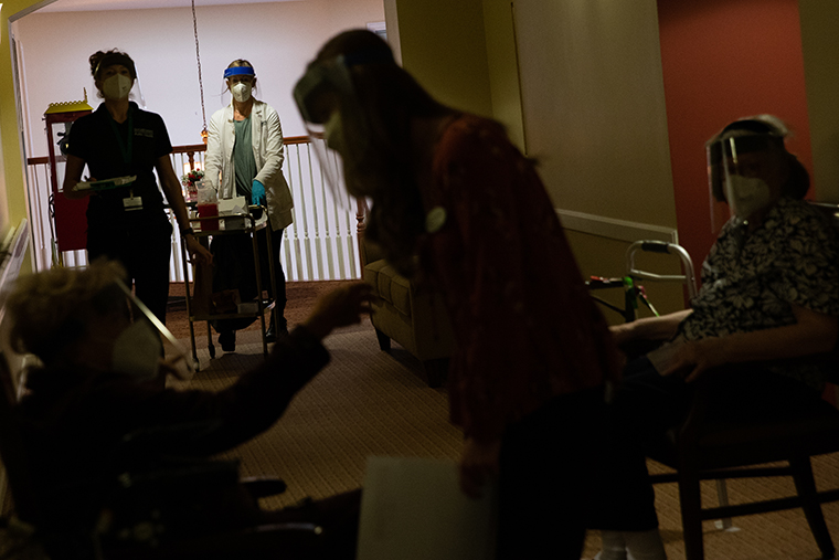 Healthcare workers arrive to distribute second doses of the Pfizer BioNtech Covid-19 vaccine to residents at a senior living facility in Bloomfield Hills, Michigan, U.S., on Friday, Jan. 22, 2021.