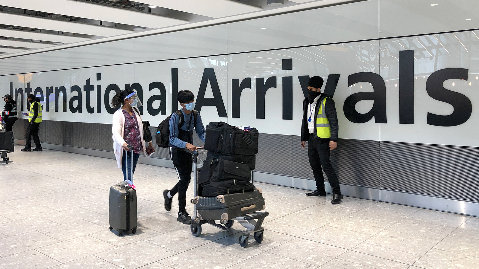 Passengers arriving from India are escorted through Heathrow airport on April 23, in London.