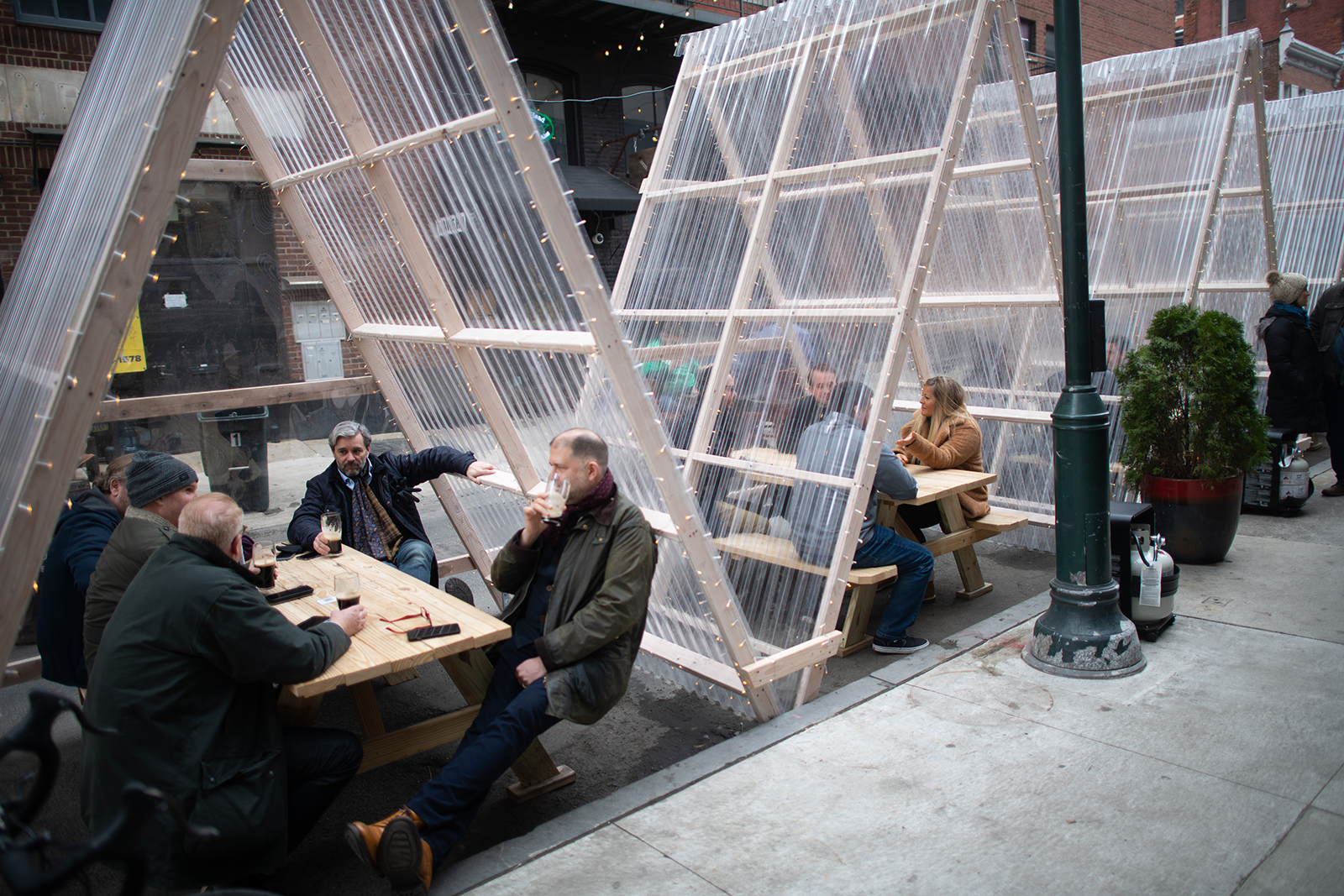 Patrons drink beer outside Fergie's Pub within plexiglass enclosures on St. Patrick's Day on March 17, in Philadelphia.