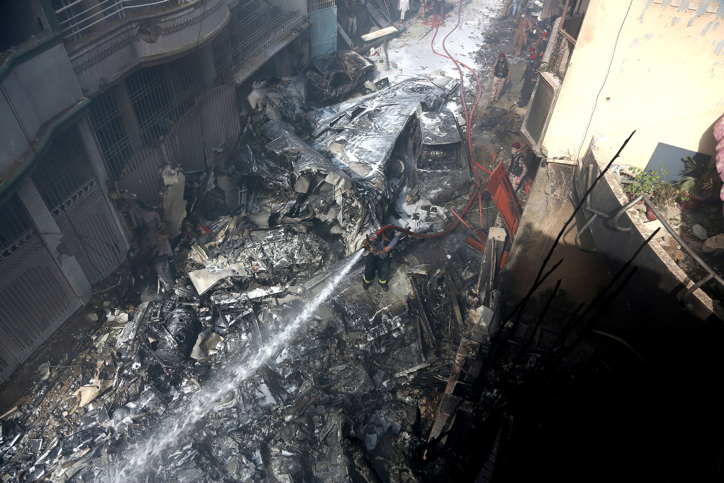 A member of a fire brigade tries to put out fire caused by a plane crash in Karachi, Pakistan, on May 22.