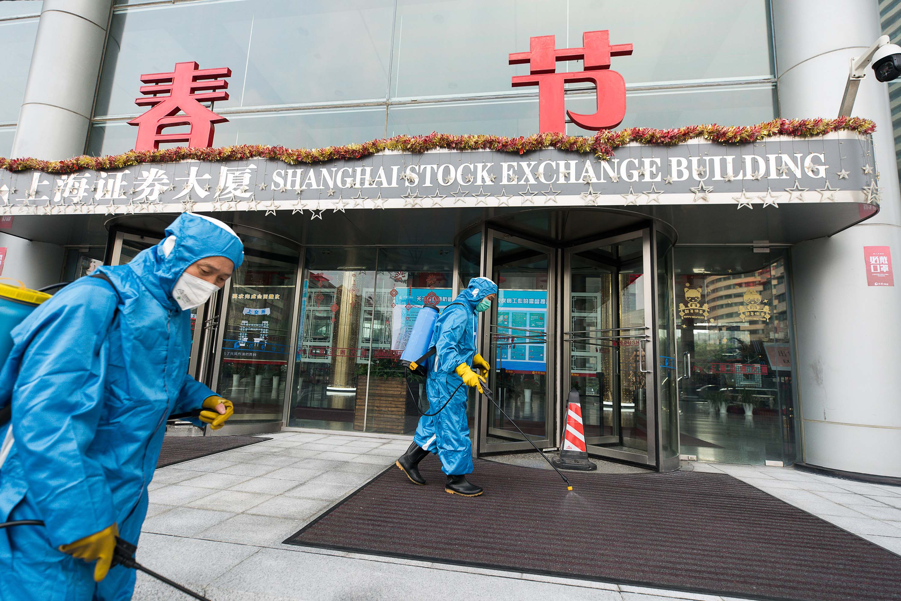 Medical workers spray antiseptic outside the Shanghai Stock Exchange Building on Monday.
