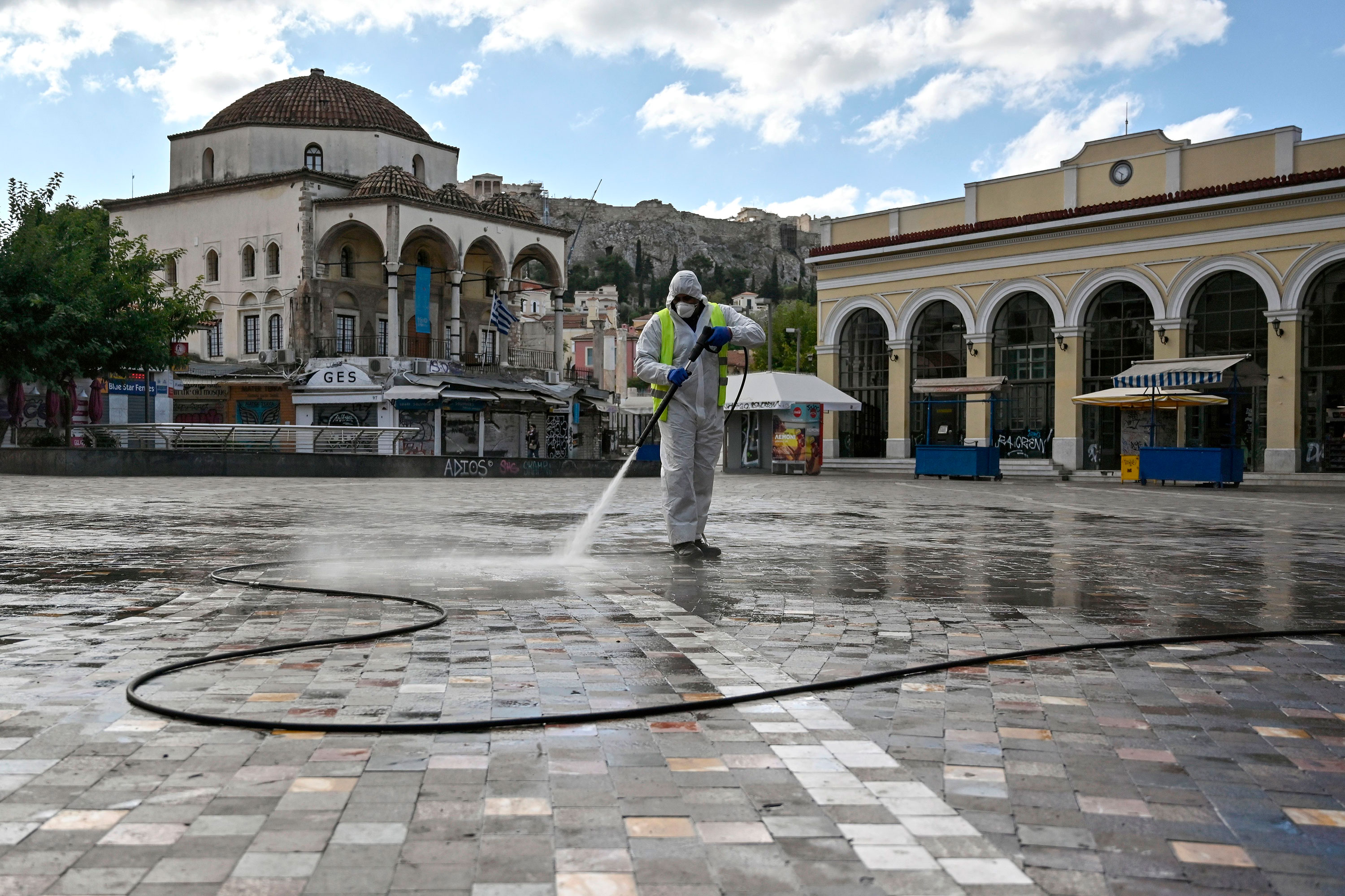 A municipal worker disinfects the empty Monastiraki square in Athens, Greece, on November 7, the first day of a three-week lockdown.
