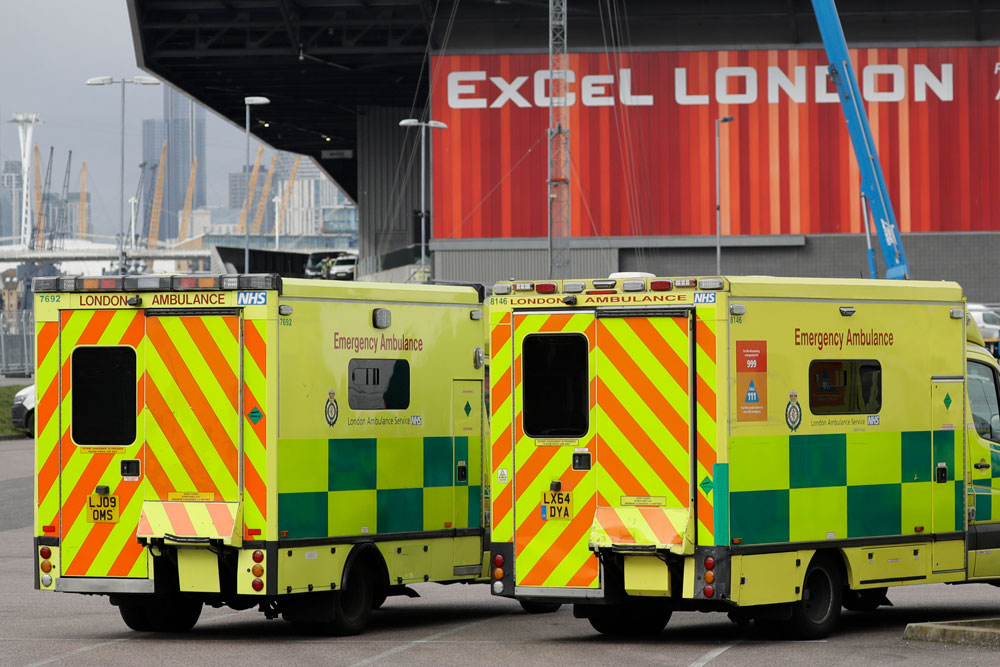 In this Monday, March 30 file photo, a line of ambulances stands outside the ExCel center, which is being turned into a 4,000-bed temporary hospital called NHS Nightingale to deal with coronavirus patients in London.