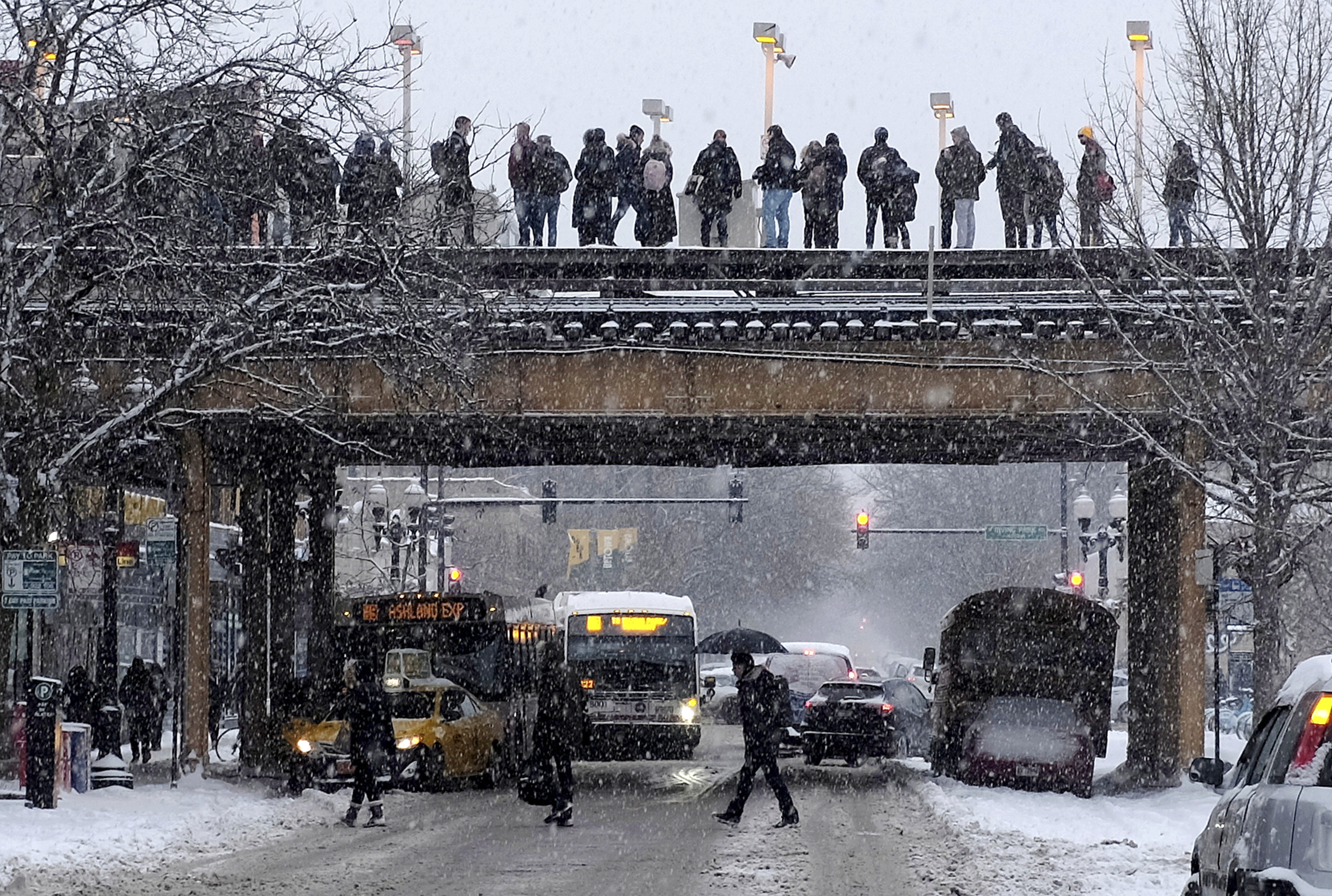 Commuters wait for a train as snow falls Monday in Chicago.