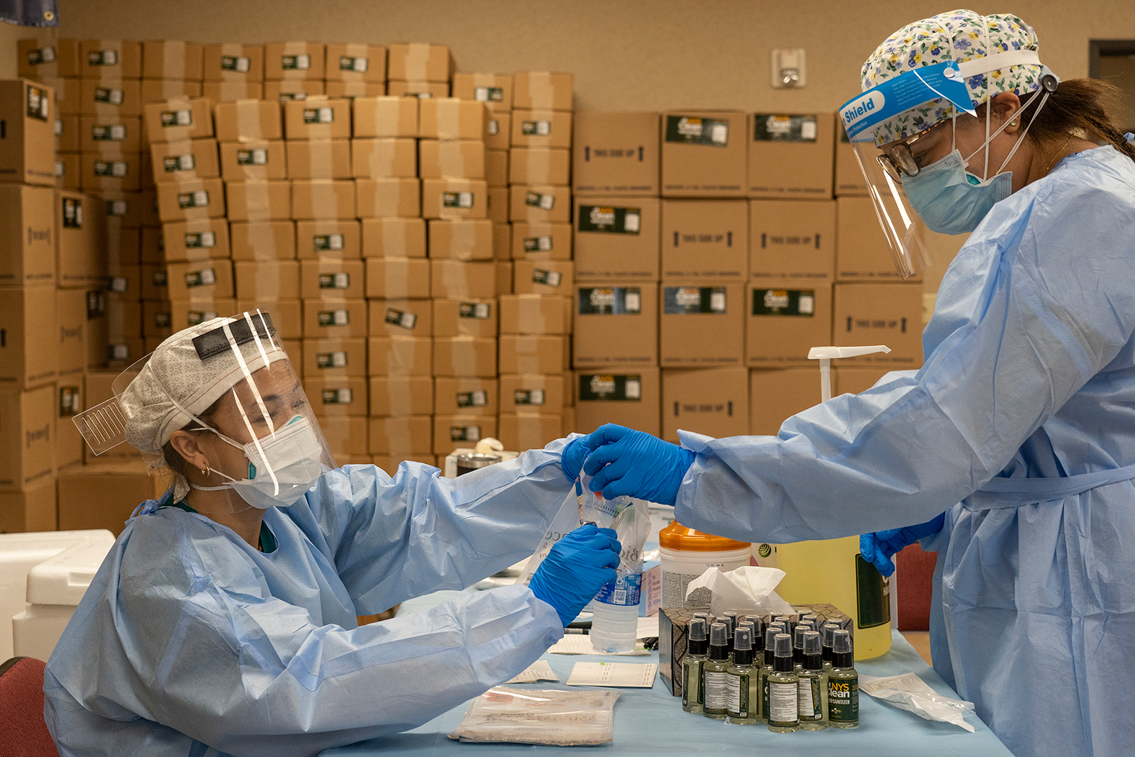 Medical workers from New York wearing personal protective equipments handle test samples at temporary testing site for Covid-19 in Higher Dimensions Church on July 17, in Houston.
