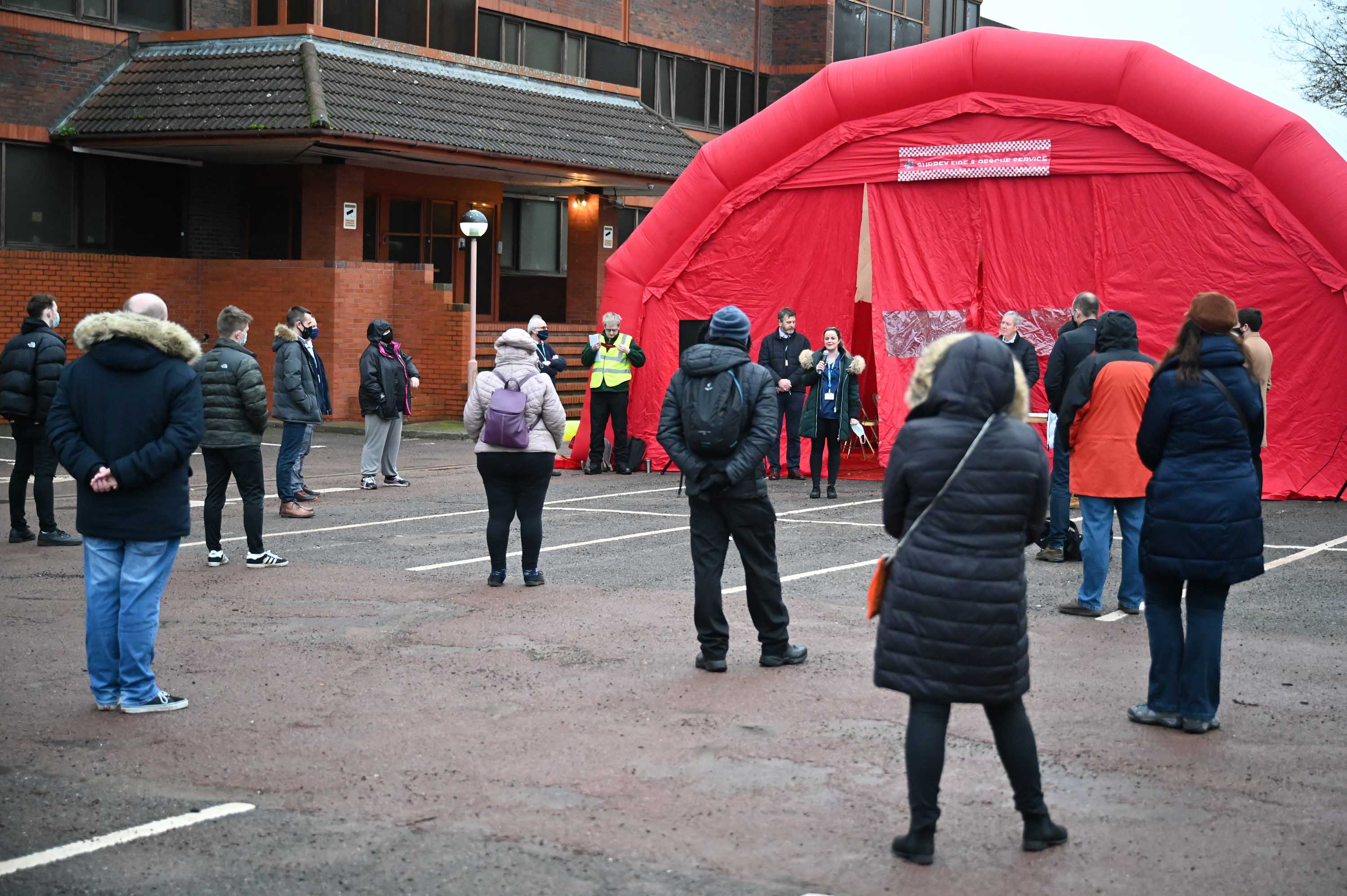 Volunteers are briefed at a fire station as local authorities prepare to deploy Covid-19 testing kits on February 2, in Woking, England.