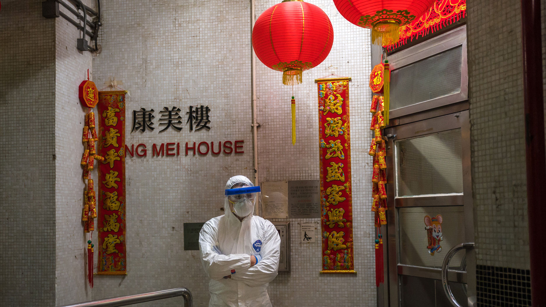 An official stands guard at an entrance to the Hong Mei House residential building in Hong Kong on Tuesday.