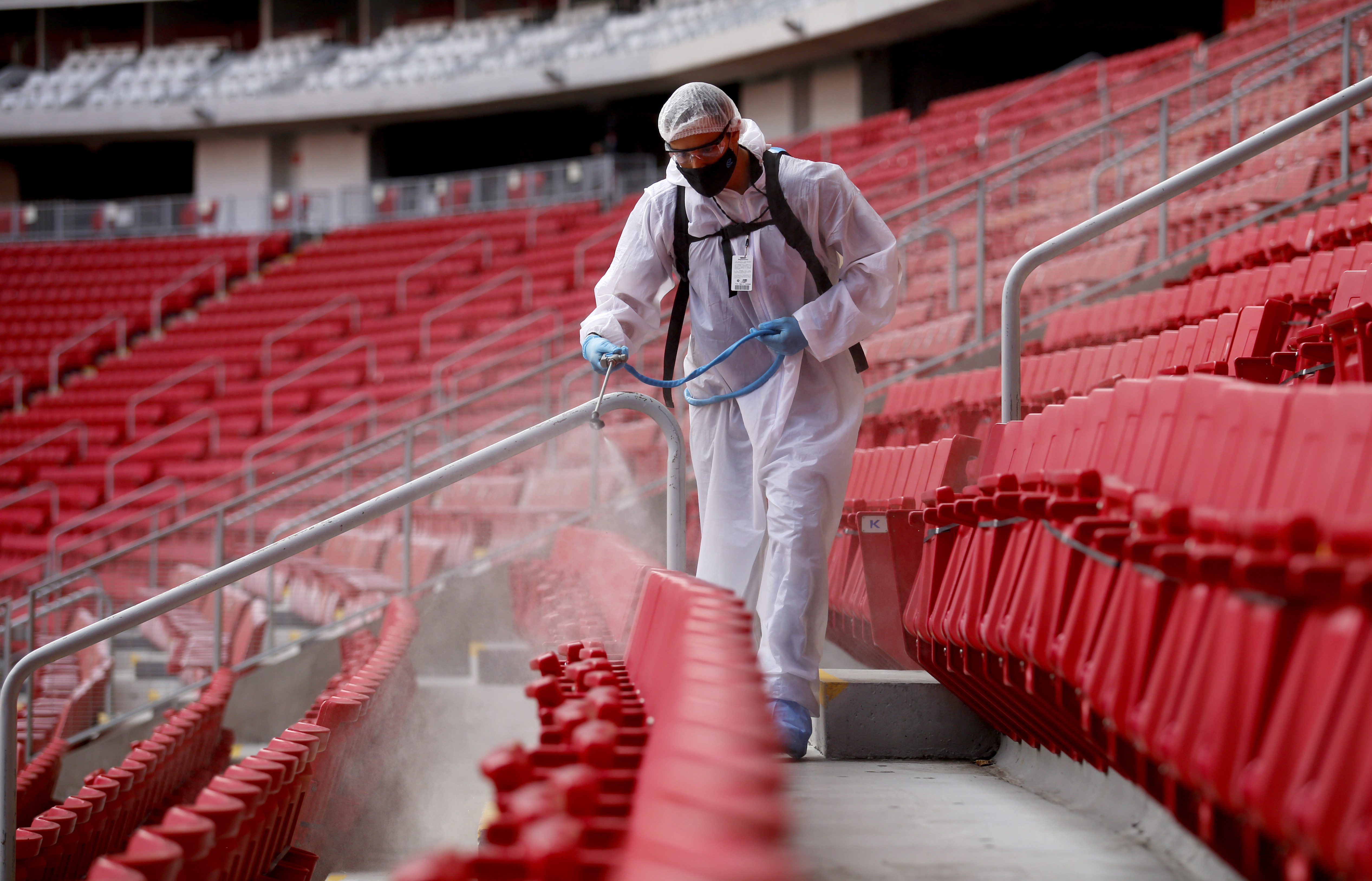 A Guadalajara staff member disinfects the stands before the start of a Mexican Apertura tournament football match between Guadalajara and Pachuca in Guadalajara, Jalisco state, Mexico, on August 29.