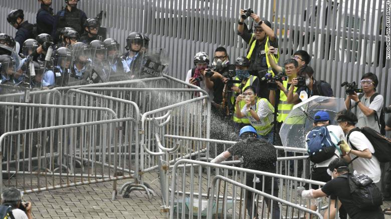 Police fire tear gas spray on protestors near Hong Kong's legislature building.