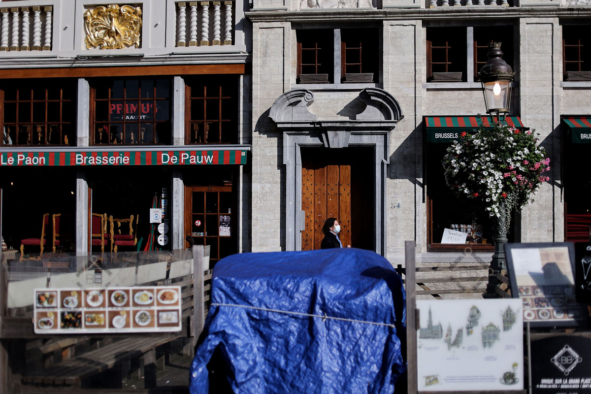 A person walks past closed restaurants at the Grand-Place in Brussels on October 19.