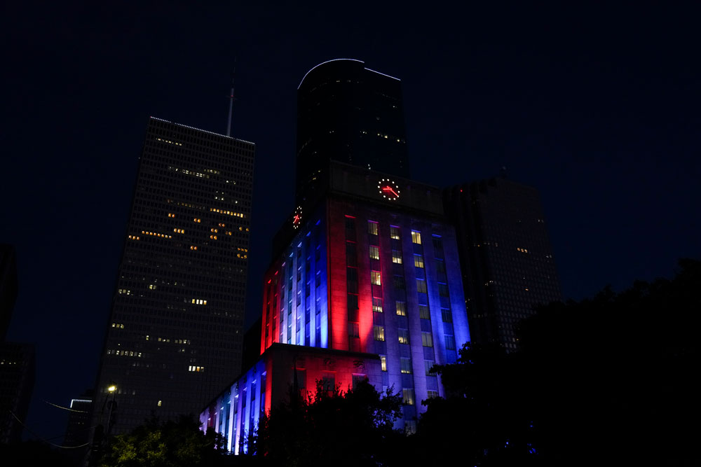 A general view of city hall in downtown Houston, Texas is seen at night, illuminated in colors, in recognition for first responders and health care professionals amid the coronavirus outbreak on Sunday, April 26.